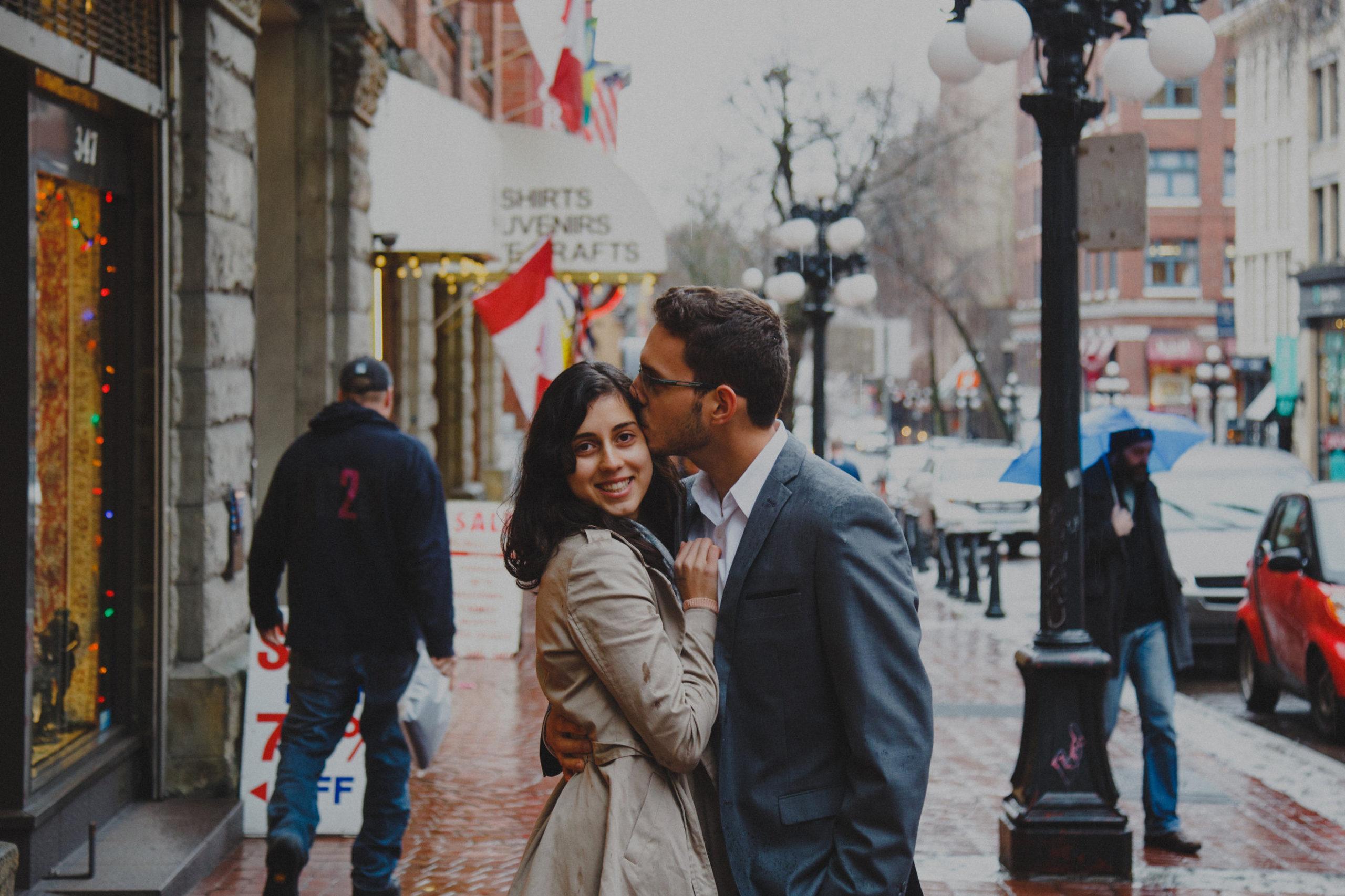 Man kisses wife on cheek on sidewalk in Gastown