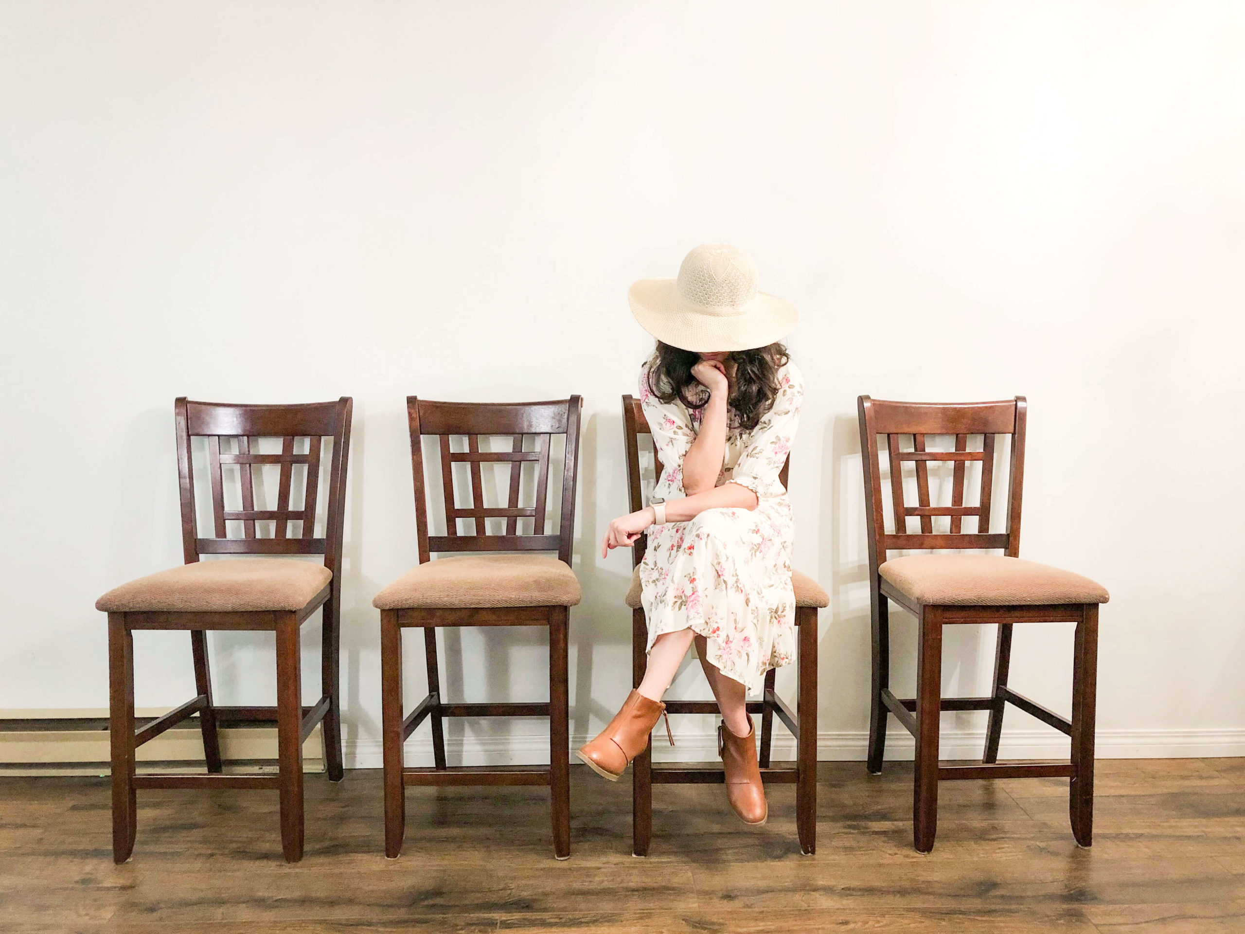 Woman wearing hat over face sits in waiting room